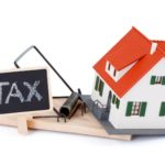 Miniature house in mousetrap of taxes, concept